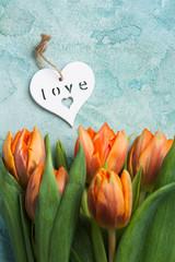 Orange tulips with wooden heart