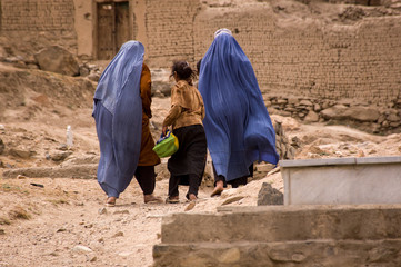 Girls and women in burqas walk through a graveyard near Kabul, Afghanistan