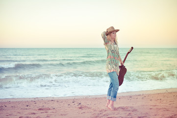 Female playing guitar on the beach background