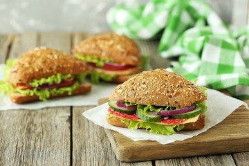 Tasty sandwiches with salami on a grey wooden background