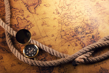 Fotobehang Schip time for adventures - vintage compass and rope on old world map