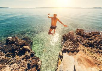 Man jumps in blue sea lagune water