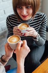 Two happy women drinking coffee at a coffee shop
