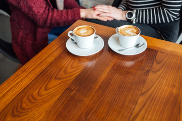 Two women and two cups of coffee on the wooden table