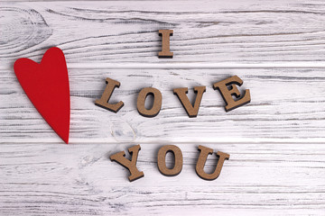 Red wood heart hanging on white painted rustic wooden background with lettering I love You