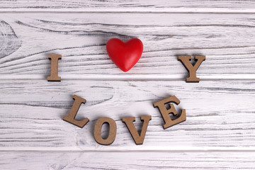 Red heart hanging on white painted rustic wooden background with lettering I love You