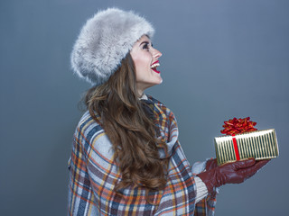 happy woman isolated on cold blue background giving present box