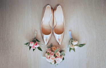 Wedding concept. bride's shoes and flowers on a wooden background