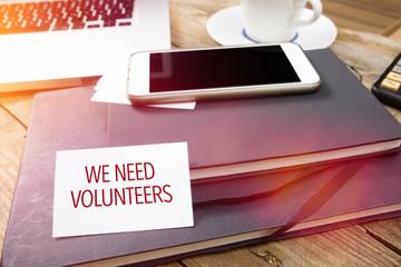 Card saying We Need Volunteers on note pad