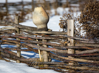 clay jug on wooden fence in winter