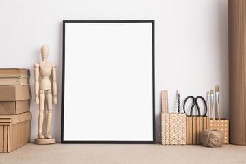Mock up with black frame on artist desk.