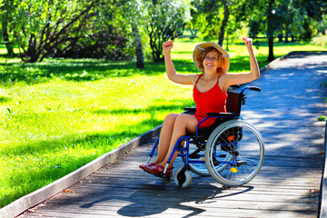 woman on wheelchair rising hands up