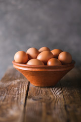 Brown eggs in a brown ceramic bowl on  wooden table on an gray abstract bbackground. Rustic Style. Eggs.  Easter photo concept. Copyspace