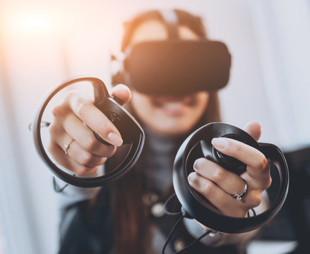 The beautifull girl playing games with virtual reality goggles