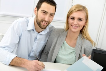 young couple signing property purchase contract