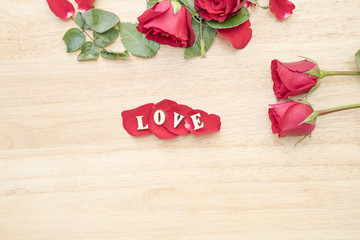 Red rose and Love word in rose on light yellow wood background,v