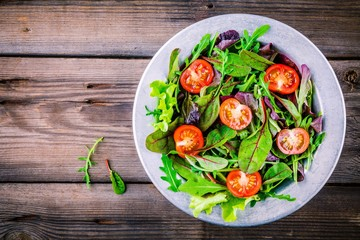 Fresh salad with mixed greens and cherry tomato on wooden background