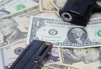 Dollar banknotes with gun and magazine