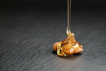 natural honey pour over almonds on slate background, with copy space