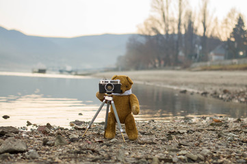Teddy bear takes photography by the riverside