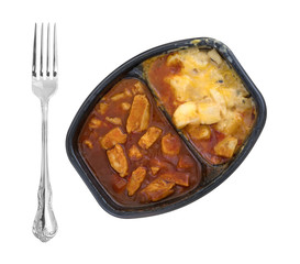 Top view of a microwaved TV dinner of chicken chunks in barbecue sauce plus potatoes and a fork to the side isolated on a white background.