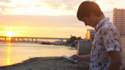 Young lonely man walking along the seashore at beautiful sunset using mobile phone