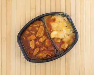 Microwaved TV dinner of chicken chunks in barbecue sauce plus potatoes atop a wood place mat top view.