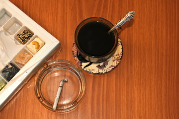 cigarette, box with sweets and сup of warm hot coffee with spoon on the table