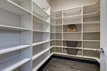 Open door to empty pantry room with white shelves