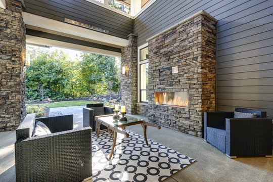 Well designed covered patio boasts stone fireplace