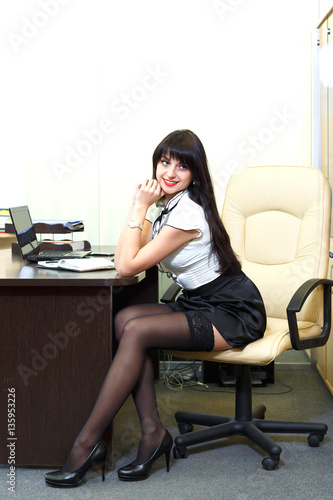 young sexy woman in black stockings sitting on workplace. Black Bedroom Furniture Sets. Home Design Ideas