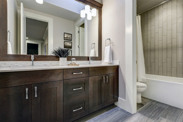 White and brown bathroom boasts a nook filled with double vanity