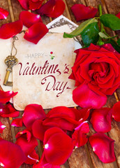 vintage background with red rose petals and gold key with happy valentines day greetings