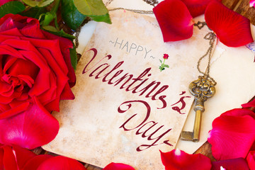 vintage background with red rose petals and antique gold key with happy valentines day greetings