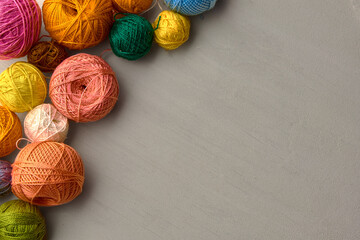 Colorful balls of yarn on white wooden background.