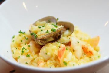 Saffron risotto with shellfish in white plate, close-up