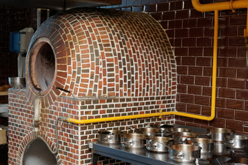 Vertical gas heated tandoor oven in restaurant kitchen