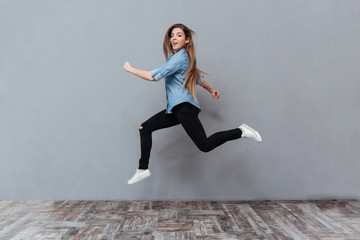 Full length image of Funny Woman jumping in studio Wall mural