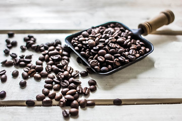 Coffee beans scattered on  rustic wood background. Arabica seeds heap at wooden table with copy space.
