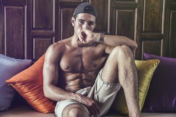 Shirtless athlete lying on pillows and looking at camera. Horizontal indoors shot.