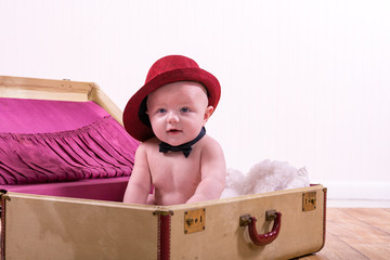 Adorable baby boy wearing a fedora and bowtie, sitting in a vintage trunk