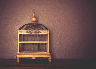 a birdcage on top of a piano toned with a retro vintage instagr