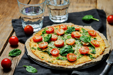 Cauliflower pizza crust with tomato and spinach