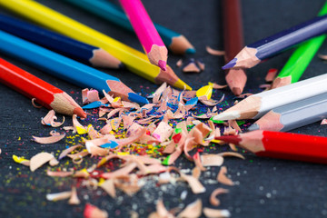 Colourful pencils with knot of wooden shavings on black surface