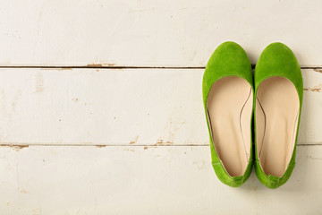 Green women's shoes (ballerinas) on wooden background.