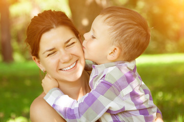 Mom and son. Child kisses his mother on nature background. Posit