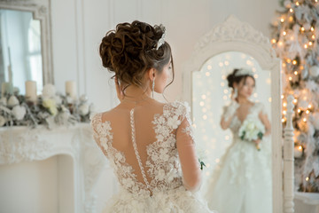 Beautiful bride in a wedding dress at a mirror in Christmas. Gir