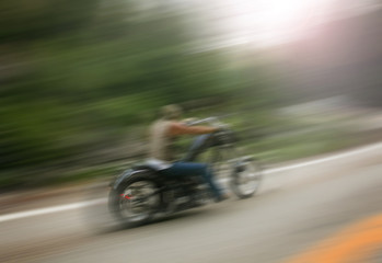 biker on mountain highway, riding around a curve with a motion b