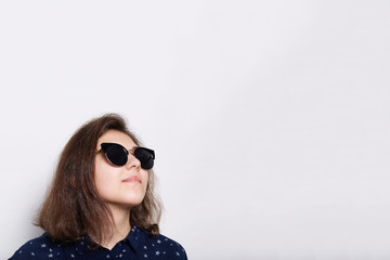 Fashion and style concept. A stylish elegant young brunette wearing sunglasses looking up isolated over white background. Portrait of attractive young model wearing sunglasses