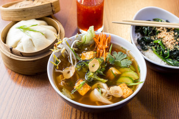 Asian dinner dishes - bao, soup and salad